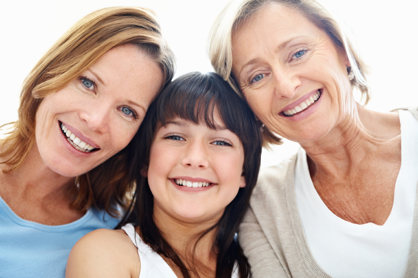 Closeup portrait of grandmother with daughter and granddaughter sitting and smiling - Indoors